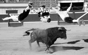 Tres recortadores realizan un salto al unísono ante uno de los toros. Fotografía: Montorio.