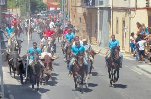 Los caballistas participantes conducen a las reses de la manada a lo largo de una de las calles de Cascante y ante la mirada de algunos espectadores. Fotografía: Rafael Villafranca.
