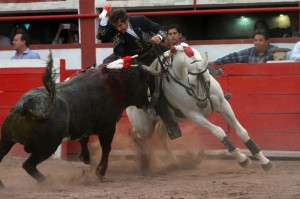 Hermoso, sobre 'Pirata' , intenta clavar una corta ante un toro que se le echa encima.