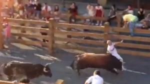 Momento en el que uno de los toros alcanza a un corredor.