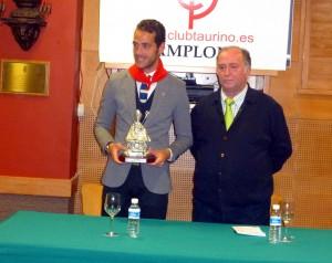 Pepe Moral con la figura de San Fermín y el pañuelo rojo que le impuso el presidente del taurino pamplonés, Juan Ignacio Ganuza, a la derecha. Fotografía: Miguel Monreal.