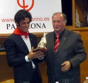 Paulita recoge la imagen de San Fermín de manos de Juan Ignacio Ganuza, presidente del Club Taurino de Pamplona.