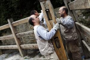 Dos operarios colocando el vallado del encierro en las calles de Pamplona el año pasado.