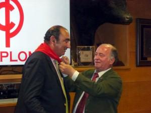 El presidente del Club Taurino de Pamplona, Juan Ignacio Ganuza, el impuso al ganadero el pañuelo rojo de la entidad.