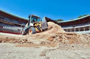Una máquina trabaja en la retirada de la arena extendida hace un año en la plaza de toros. Fotografía: Calleja.