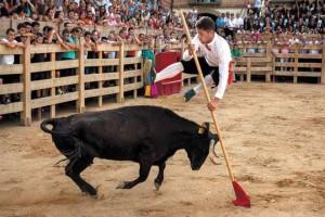 José Manuel González Nieto, el Poca, saltando con garrocha sobre la vaquilla 'Fogonera'. Fotografía: Carmona.