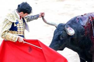 López Simón agarra el pitón derecho de un toro de Jandilla en la plaza de Pamplona.