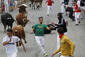 Josu López, de blanco, se duele en el suelo. El toro también cayó. El otro corredor arrollado, de negro, sale por su pie. Fotografía: Eduardo Buxens.