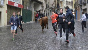 Varios mozos corren delante de una de las vacas del encierrillo, en la plaza Santiago, bajo la lluvia. Fotografía: Susana Exparza.