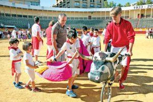 Un niño, asesorado por Pablo García, da un capotazo al toro simulado. Fotografía: Nuria G. Landa.