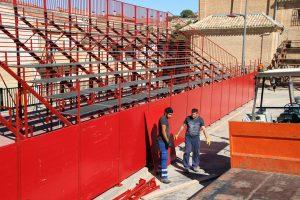 Dos miembros de la brigada trabajan en el montaje de la nueva plaza de toros portátil de Milagro. Fotografía: Enrique Pejenaute.