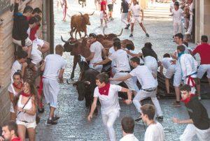 Los jóvenes deshacen la barricada de la plaza de Santiago con la llegada de las vacas en el encierro de ayer. Fotografía: Montxo A. G.