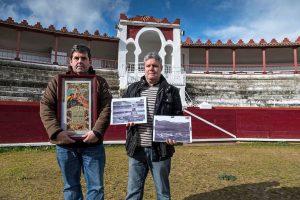 Juan José Crespo y Roberto Ojer, presidente y secretario del Club Taurino Estellés respectivamente, en la plaza de Estella con un cartel y fotografías antiguas. Fotografía: Montxo A. G.