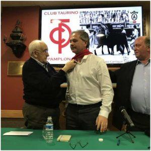 Emilio García San Miguel impone el pañuelo rojo a Fabrice Torrito ante la presencia de Ignacio Ganuza, presidente del Club Taurino de Pamplona.