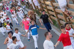 El mozo Íñigo Jiménez Mayor - con camiseta rosa-, instantes antes de ser arrollado por la manada. Fotografía: Blanca Aldanondo.