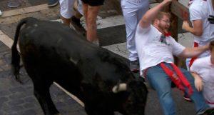 Momento en el que el toro cornea y voltea a un corredor.
