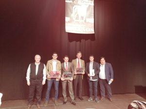 Los tres premiados, en el centro de la imagen, con sus respectivos trofeos.