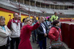 Un grupo de tuirstas escucha atento las explicaciones de una guía en la plaza de toros de Pamplona.