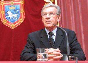 Jean Grenet, en una de sus visitas a Pamplona, con el escudo de Pamplona al fondo.